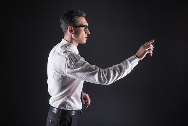 Mente afiada. homem bonito e inteligente usando óculos e usando o painel do computador enquanto trabalha com eletrônicos modernos