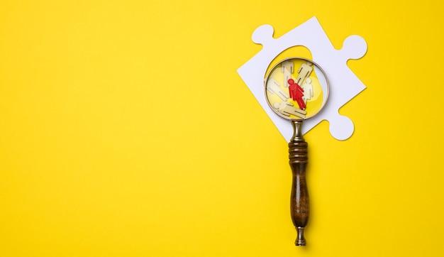 Mentira de homenzinhos de madeira e uma lupa de madeira sobre um fundo amarelo. conceito de busca de pessoas talentosas e únicas, recrutamento de pessoal, identificação de pessoas capazes de progredir na carreira