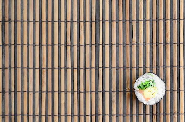 Mentira de rolo de sushi em um fundo de esteira serwing palha de bambu