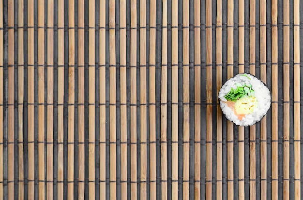 Mentira de rolo de sushi em um tapete de serwing de palha de bambu