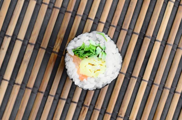 Mentira do rolo de sushi em uma esteira de serwing de bambu da palha. comida asiática tradicional. vista do topo.