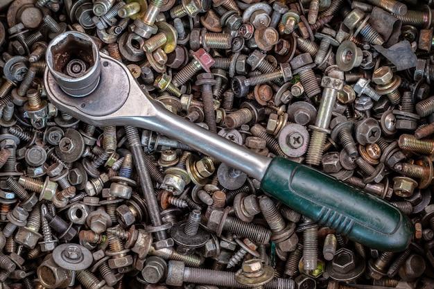 Mentira plana catraca de metal lay no fundo de várias rodas dentadas de metal, parafusos e pregos, vista superior. kit de ferramentas de carpinteiro de close-up