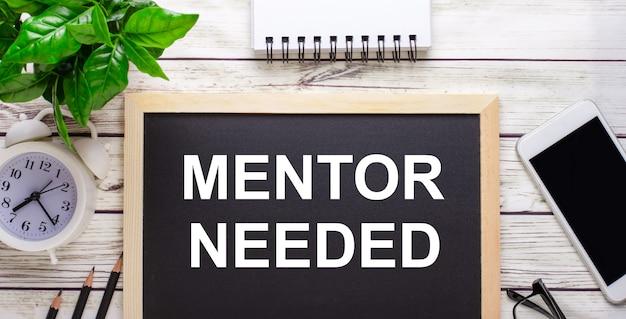 Mentor necessário escrito em uma superfície preta perto de lápis, um smartphone, um bloco de notas branco e uma planta verde em um vaso
