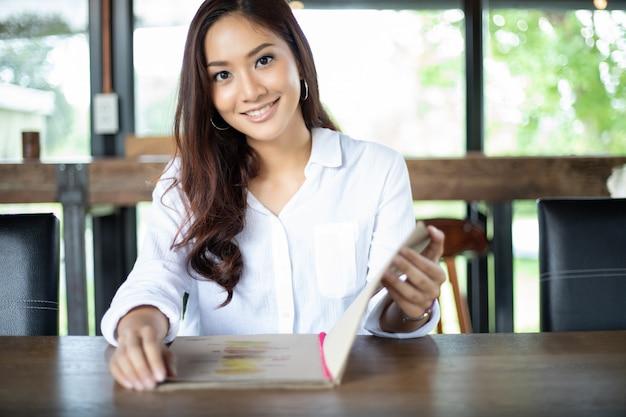 Menu aberto mulher asiática para encomendar no café café e restaurante e sorrindo