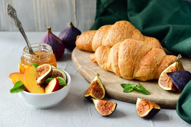 Menu de café da manhã com croissant, geléia de maçã fresca e salada de frutas