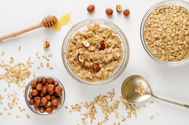 Menu de comida de dieta equilibrada no café da manhã com tigela de mingau de aveia com avelãs e mel