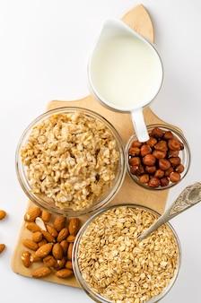 Menu de comida de dieta para café da manhã com tigela de aveia com nozes e jarra de leite na placa de madeira