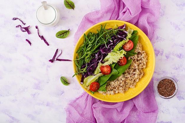 Menu de dieta. estilo de vida saudável. mingau de aveia e legumes frescos - tomate, espinafre, rúcula, couve roxa e alface no prato. postura plana. vista do topo