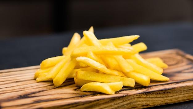 Menu de fast food. batatas fritas salgadas tradicionais na placa de madeira rústica.