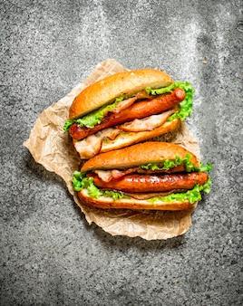 Menu de fast food. churrasco de carne de cachorro-quente com ervas, ketchup e mostarda quente em mesa rústica.