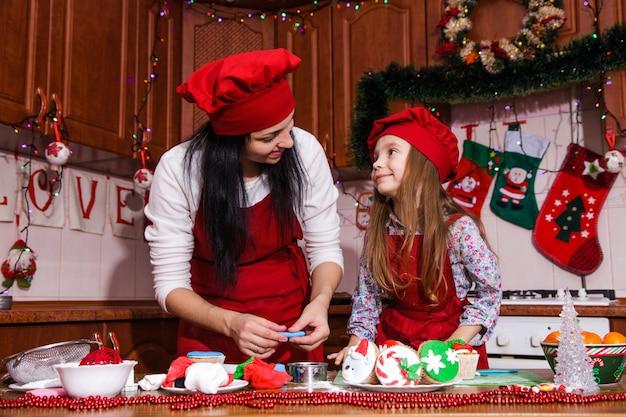 Menu de jantar de festa de natal idéia de sobremesa cupcakes de chocolate com menta creme de leite polvilhar decoração mãe filha ano novo avental vermelho chef chefe confeiteiro
