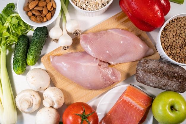 Menu de proteínas, carne, vegetais frescos, frutas e nozes, alimentos saudáveis em fundo de pedra branca