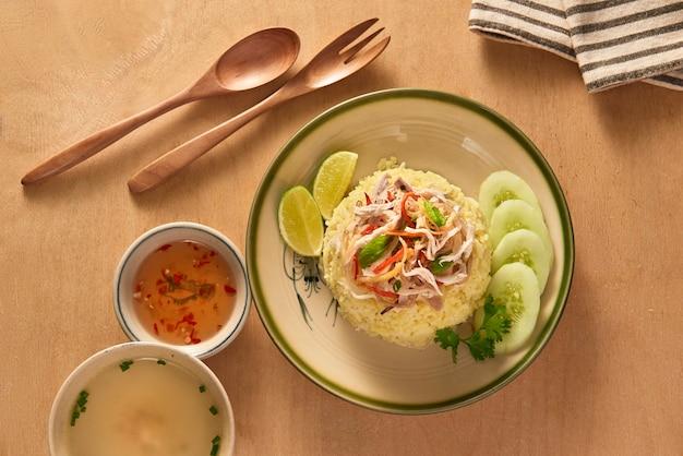 Menu de restaurante de comida vietnamita exótica de perto. prato asiático tradicional servido em prato branco. carne de frango branco cozido picado, pepino verde e cenoura com arroz