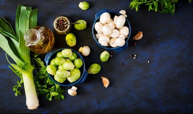 Menu dietético. ingredientes: legumes - couve de bruxelas, cogumelos, alho-poró e ervas em um fundo escuro. vista do topo. menu de legumes.