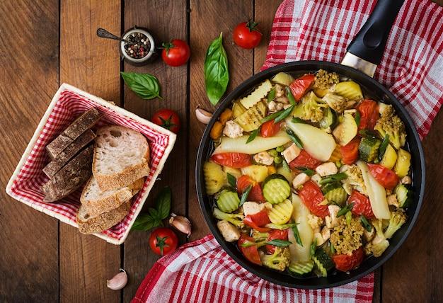 Menu dietético. legumes no vapor com filé de frango na panela em cima da mesa de madeira. vista do topo