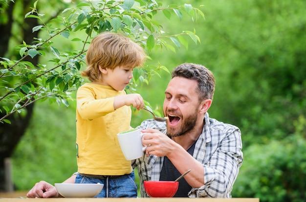 Menu infantil. família gosta de comida caseira. hábitos alimentares. menino com pai comendo fundo de natureza de alimentos. café da manhã de verão. conceito de comida saudável. pai, filho, comem e se divertem. alimentando bebê.