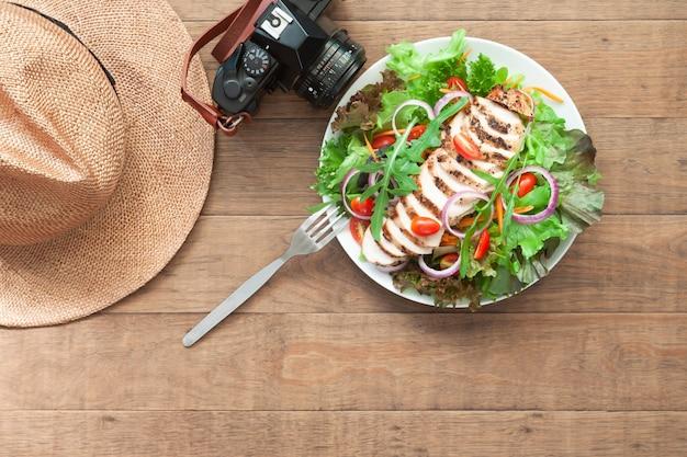 Menu saudável da vista superior com câmera e chapéu na tabela de madeira. conceito de bem-estar e estilo de vida