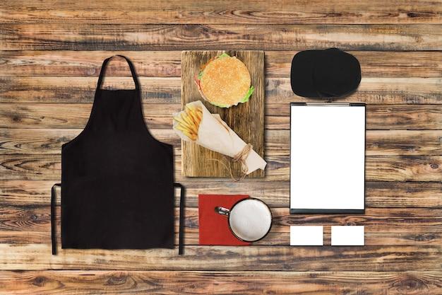 Menu vazio e cartões de visita com hambúrguer em uma mesa de restaurante