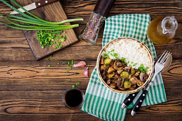 Menu vegano. comida dietética. arroz cozido com cogumelos e couve de bruxelas em estilo asiático. vista do topo. postura plana.