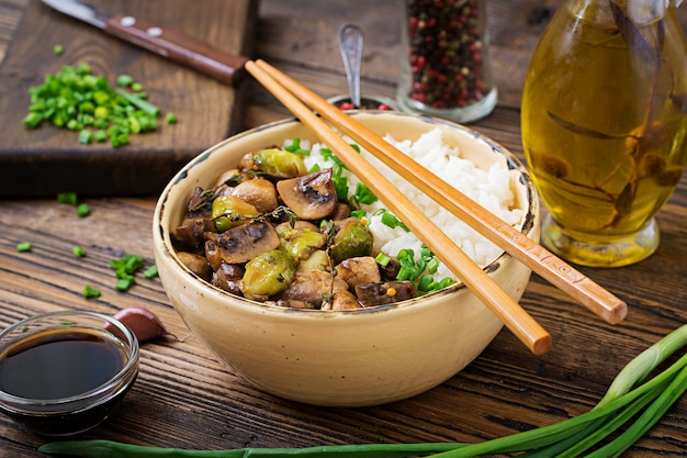 Menu vegano. comida dietética. arroz cozido com cogumelos e couve de bruxelas em estilo asiático.