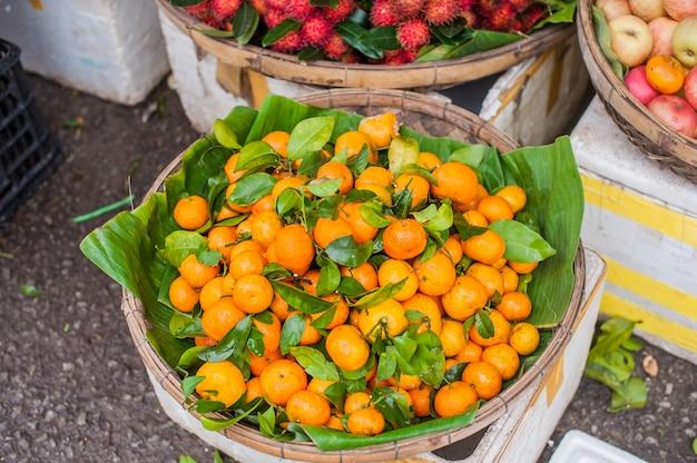 Mercado asiático do fazendeiro que vende o mandarino fresco em hoi an, vietnã. cores laranja e verde.