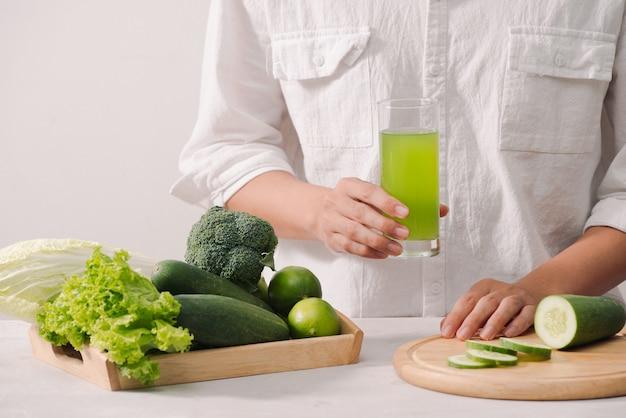 Mercado. comida vegana saudável. legumes frescos, bagas, verduras e frutas em bandeja de madeira: pepinos, rabanete ervilhas verdes ... mesa branca. nas mãos do homem copie o espaço