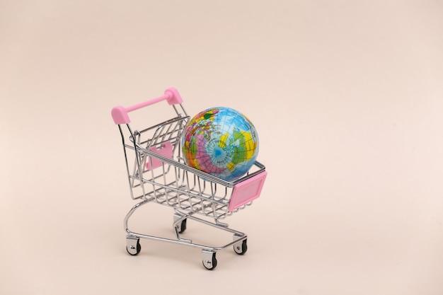 Mercado global. mini carrinho de compras com globo em fundo bege