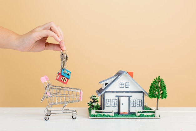 Mercado imobiliário com casa e mini casa no carrinho de compras