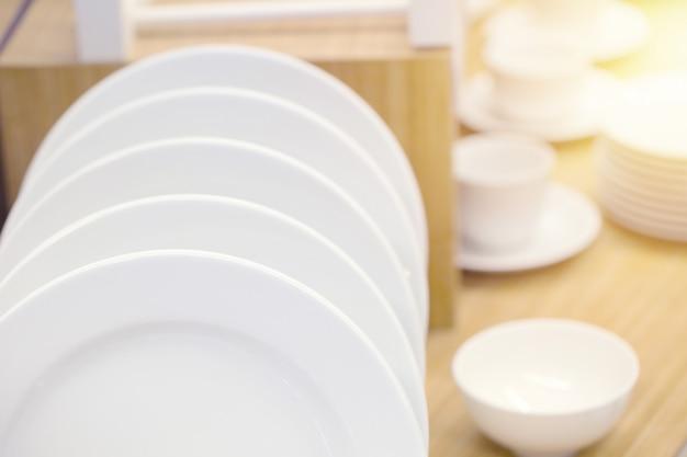 Mercadorias limpos brancos do prato da cozinha cerâmica decorativos na madeira