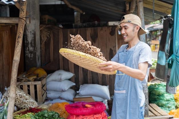 Mercearia asiática segurando uma bandeja de bambu, peneirando açafrão para limpar em uma barraca de legumes