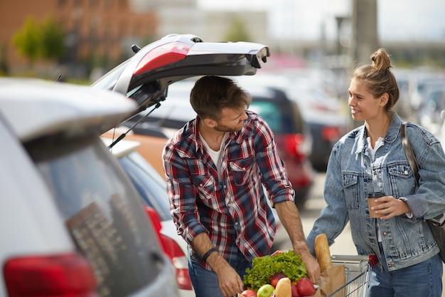 Mercearia de embalagem de casal no carro