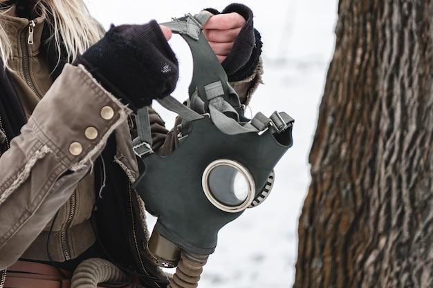 Mercenário militar coloca uma máscara de gás na rua.