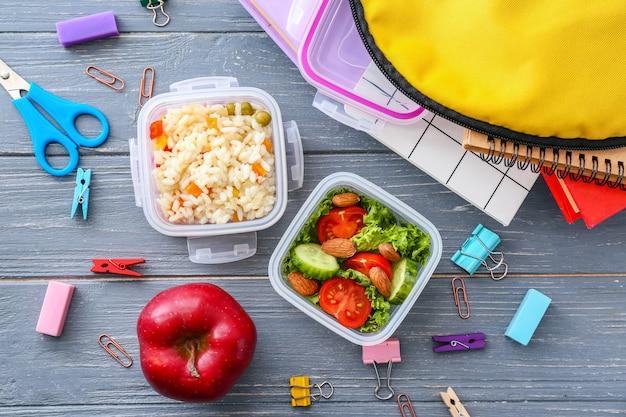 Merenda escolar com comida saborosa e papelaria em madeira