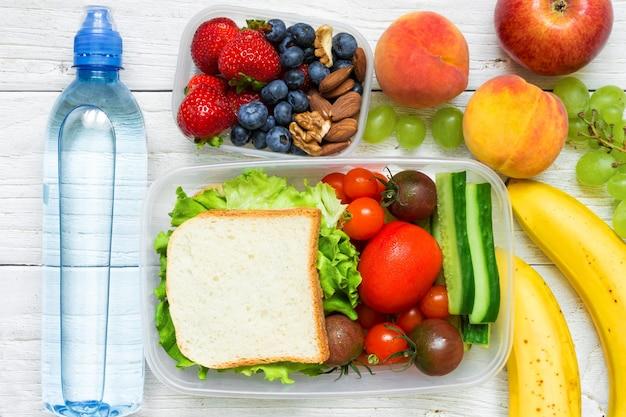 Merenda escolar com sanduíche, frutas e vegetais frescos