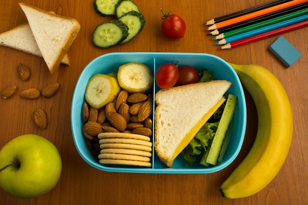 Merenda escolar e ingredientes na caixa em cima da mesa. vista superior.