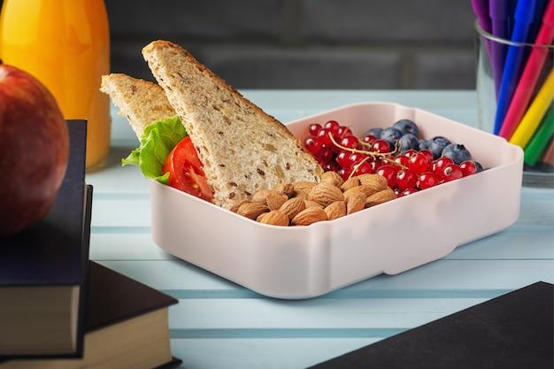 Merenda escolar em uma caixa, frutas, nozes e um sanduíche.