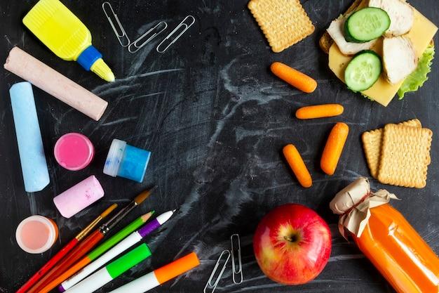 Merenda escolar, maçã vermelha, sanduíche aberto, suco, biscoitos, cenouras e material escolar no quadro-negro. nutrição saudável para crianças. férias escolares. vista superior e espaço de cópia