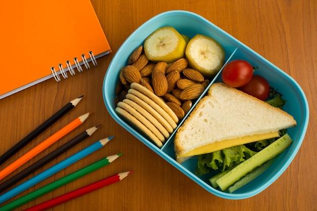 Merenda escolar na caixa, lápis e caderno em cima da mesa. vista superior.