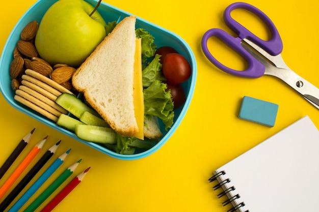 Merenda escolar na caixa, lápis e caderno