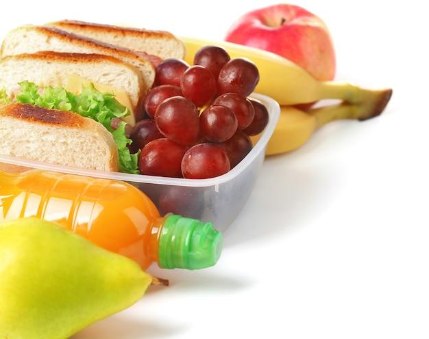 Merenda escolar saudável com sanduíche, frutas e suco isolado no branco