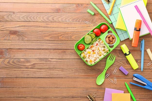 Merendeira escolar com comida saborosa e artigos de papelaria com fundo de madeira