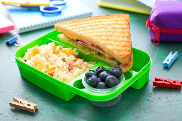 Merendeira escolar com comida saborosa e papelaria na mesa
