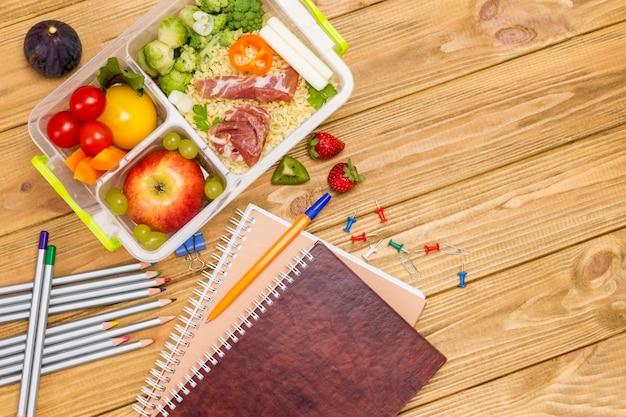 Merendeira escolar com comida saborosa e papelaria