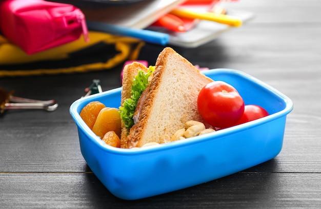 Merendeira escolar com comida saborosa em fundo de madeira