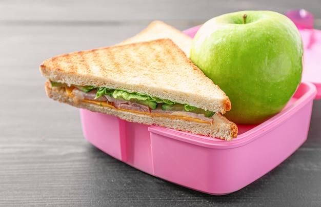 Merendeira escolar com comida saborosa em madeira