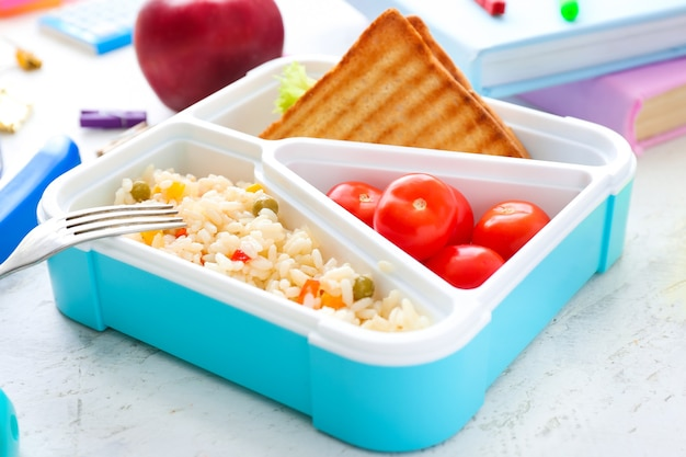 Merendeira escolar com comida saborosa na mesa