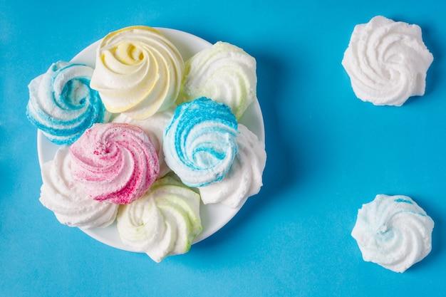 Merengue colorido doce caseiro sobre fundo azul. sobremesa.