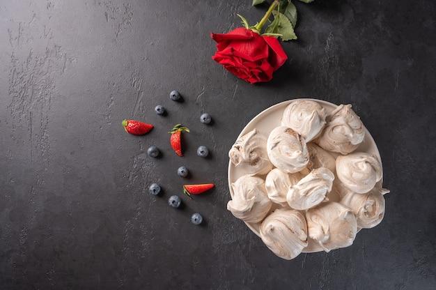 Merengue de sobremesa popular caseiro em um prato branco sobre uma superfície preta