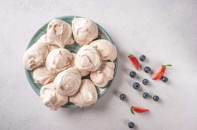 Merengue de sobremesa popular caseiro no prato sobre uma superfície clara