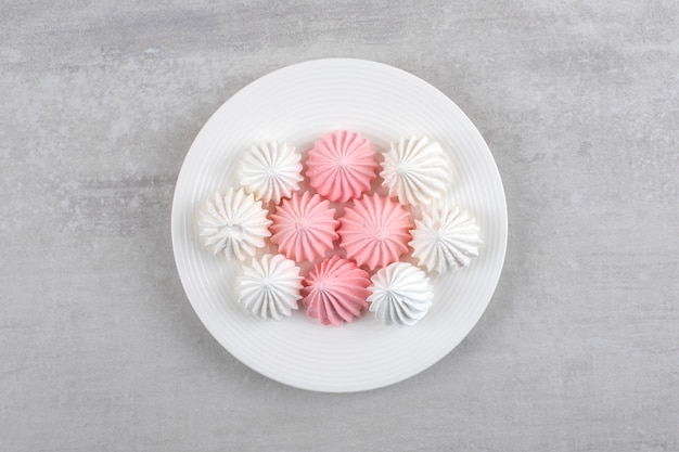 Merengue rosa e branco em um prato branco, na mesa de mármore.